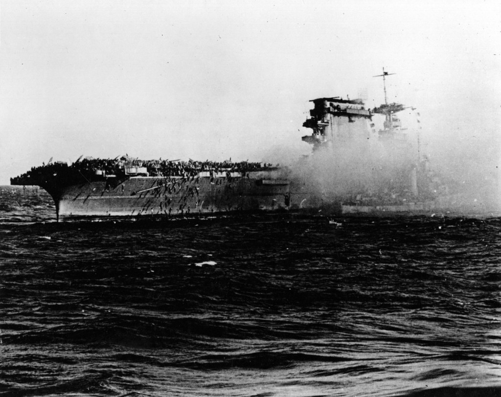 A destroyer alongside USS Lexington (CV-2) as the carrier is abandoned during the afternoon of 8 May 1942. Note crewmen sliding down lines on Lexington's starboard quarter. Credit: U.S. Navy