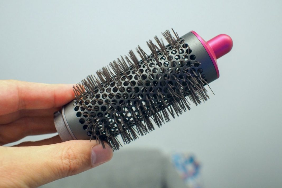 The round brush has perforations for air flow.