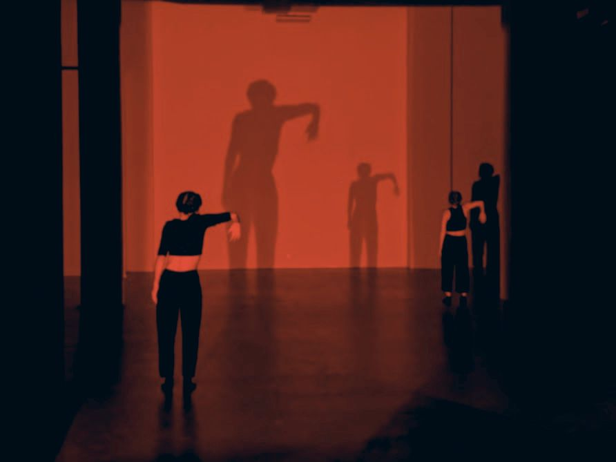 Dancers play with shadow as noises from a nearby sound bath echo in a cavernous room.