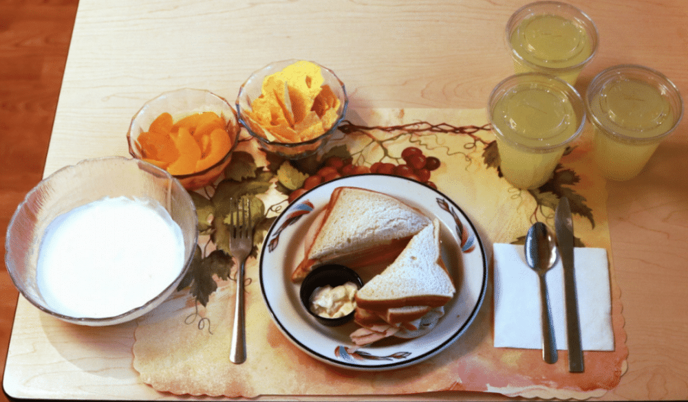 A meal sits on a placemat. A sandwich on white bread, two small bowls with peaches and chips, a large bowl of yogurt, and three cups of lemonade.